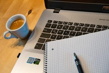 cup of tea in blue mug with a pen placed on a the surface of a pad of paper on top of a laptop keyboard